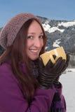 Молодая женщина выпивая чашку горячего чая в горах в зиме Стоковое фото RF