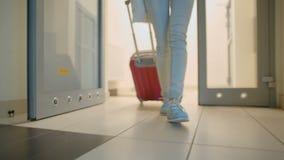 Молодая женщина выходя лифт и строя к улице с чемоданом и сумкой сток-видео