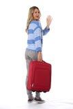 Молодая женщина выходя с красным чемоданом Стоковое фото RF
