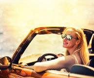Молодая женщина в автомобиле cabriolet около моря Стоковая Фотография