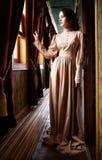 Молодая женщина в бежевом винтажном платье дежурного начала двадцатого века Стоковая Фотография RF