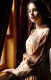 Молодая женщина в бежевом винтажном платье дежурного начала двадцатого века стоковое фото rf