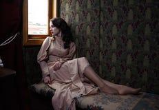 Молодая женщина в бежевом винтажном платье усаживания начала двадцатого века Стоковая Фотография RF