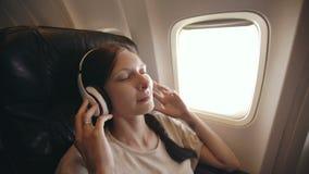 Молодая женщина в беспроволочных наушниках слушая к музыке и усмехаясь во время мухы в самолете