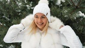 Молодая женщина в белом платье замерзает под елевым и усмехаться видеоматериал