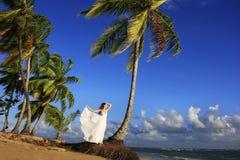 Молодая женщина в белом платье на пляже стоковые изображения rf