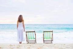 Молодая женщина в белом платье представляя на пляже Стоковая Фотография RF