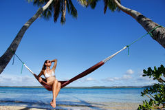 Молодая женщина в бикини сидя в гамаке между пальмами, o Стоковые Фотографии RF