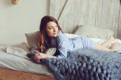 Молодая женщина в бодрствовании пижамы вверх в утре в уютной скандинавской спальне и лежать на кровати с сверхразмерным связанным стоковое изображение