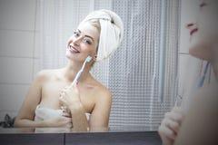 Молодая женщина в ванной комнате чистя ее зубы щеткой с острословием зубной щетки Стоковое фото RF