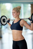 Молодая женщина в весах спортзала фитнеса поднимаясь Стоковое Изображение