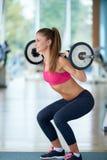 Молодая женщина в весах спортзала фитнеса поднимаясь Стоковое Изображение RF