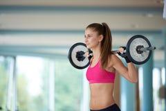 Молодая женщина в весах спортзала фитнеса поднимаясь Стоковые Изображения