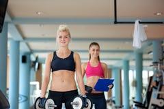 Молодая женщина в весах спортзала фитнеса поднимаясь Стоковые Изображения RF