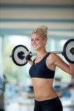 Молодая женщина в весах спортзала фитнеса поднимаясь Стоковые Фото