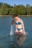 Молодая женщина в волосах обрызгивания бикини в озере стоковые изображения