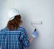 Молодая женщина в вскользь одеждах перед белой стеной стоковое изображение rf