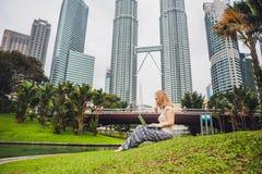 Молодая женщина в вскользь платье используя компьтер-книжку в тропическом парке на предпосылке небоскребов компьтер-книжка чашки  Стоковое фото RF