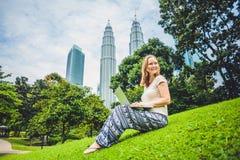 Молодая женщина в вскользь платье используя компьтер-книжку в тропическом парке на предпосылке небоскребов компьтер-книжка чашки  Стоковое Изображение RF