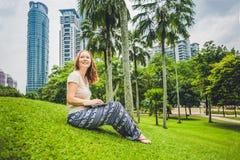 Молодая женщина в вскользь платье используя компьтер-книжку в тропическом парке на предпосылке небоскребов компьтер-книжка чашки  Стоковое Изображение