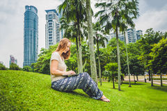 Молодая женщина в вскользь платье используя компьтер-книжку в тропическом парке на предпосылке небоскребов компьтер-книжка чашки  Стоковые Фото