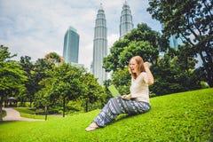 Молодая женщина в вскользь платье используя компьтер-книжку в тропическом парке на предпосылке небоскребов компьтер-книжка чашки  Стоковые Изображения RF
