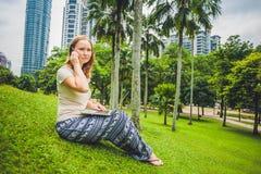 Молодая женщина в вскользь платье используя компьтер-книжку в тропическом парке на предпосылке небоскребов компьтер-книжка чашки  Стоковые Изображения