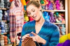 Молодая женщина в вязать магазине с круговой иглой стоковая фотография rf