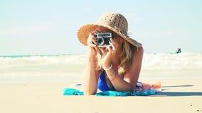 Молодая женщина в голубом бикини лежит на пляже с винтажной камерой и имеет шляпу солнца дальше акции видеоматериалы