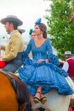 Молодая женщина в голубом платье верхом Стоковое фото RF