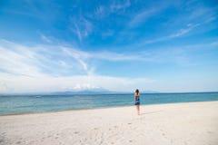 Молодая женщина в голубом платье идя на пляж тропического острова Nusa Lembongan, Индонезии Изумительное небо, вид на океан Стоковая Фотография RF