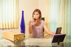 Молодая женщина в депрессии, выпивая спирте Стоковое Фото