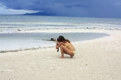 Молодая женщина в желтом бикини делает фотографии на пляже Стоковые Изображения RF