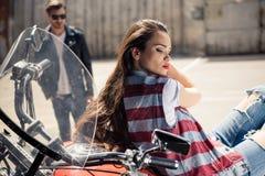Молодая женщина в жилете джинсовой ткани сидя на мотоцикле и стильном человеке в солнечных очках стоя позади Стоковая Фотография