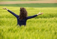 Молодая женщина в зеленом пшеничном поле стоковые изображения