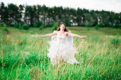 Молодая женщина в изображении ангела стоит на холме с поднятыми руками стоковая фотография rf