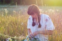 Молодая женщина в длинной рубашке вышитой белизной соткет венок Стоковые Изображения