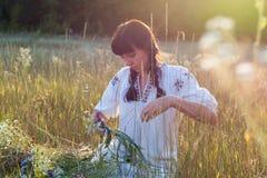 Молодая женщина в длинной рубашке вышитой белизной соткет венок Стоковое Изображение
