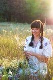 Молодая женщина в длинной рубашке вышитой белизной соткет венок Стоковое Изображение RF