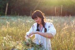 Молодая женщина в длинной рубашке вышитой белизной соткет венок Стоковое Фото