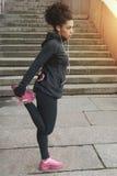 Молодая женщина в идущих одеждах протягивая ее ногу Стоковые Изображения RF
