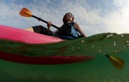 Молодая женщина в каяке на океане Стоковое Фото
