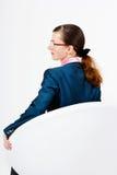 Молодая женщина в костюме и стеклах сидя в стуле Стоковые Фото