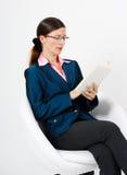 Молодая женщина в костюме и стеклах читая книгу Стоковые Изображения RF