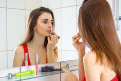 Молодая женщина в красной рубашке красит губы губной помады Стоковые Фотографии RF