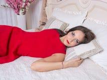 Молодая женщина в красном платье на кровати стоковые фотографии rf
