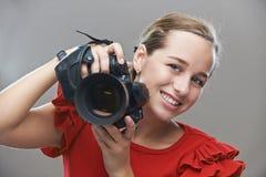 Молодая женщина в красном платье с камерой стоковое фото rf