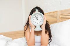 Молодая женщина в кровати дома с будильником стоковое фото