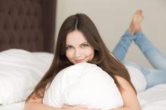 Молодая женщина в кровати смотря камеру, предназначенный для подростков портрет девушки Стоковое Изображение