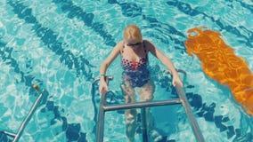 Молодая женщина в купальнике тренирует тот специальный имитатор в бассейне Гимнастика Aqua и спорт, здоровый образ жизни акции видеоматериалы